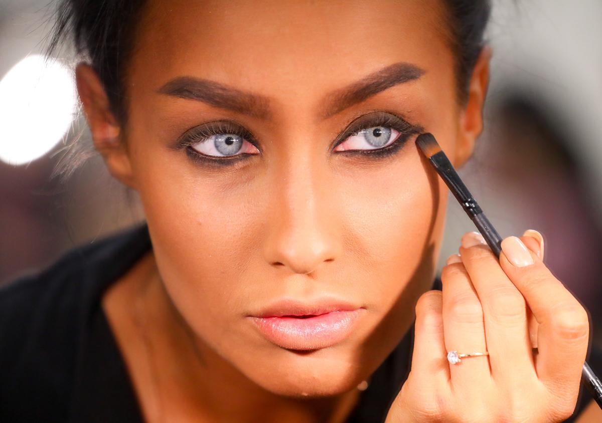 A woman applies black eyeshadow.