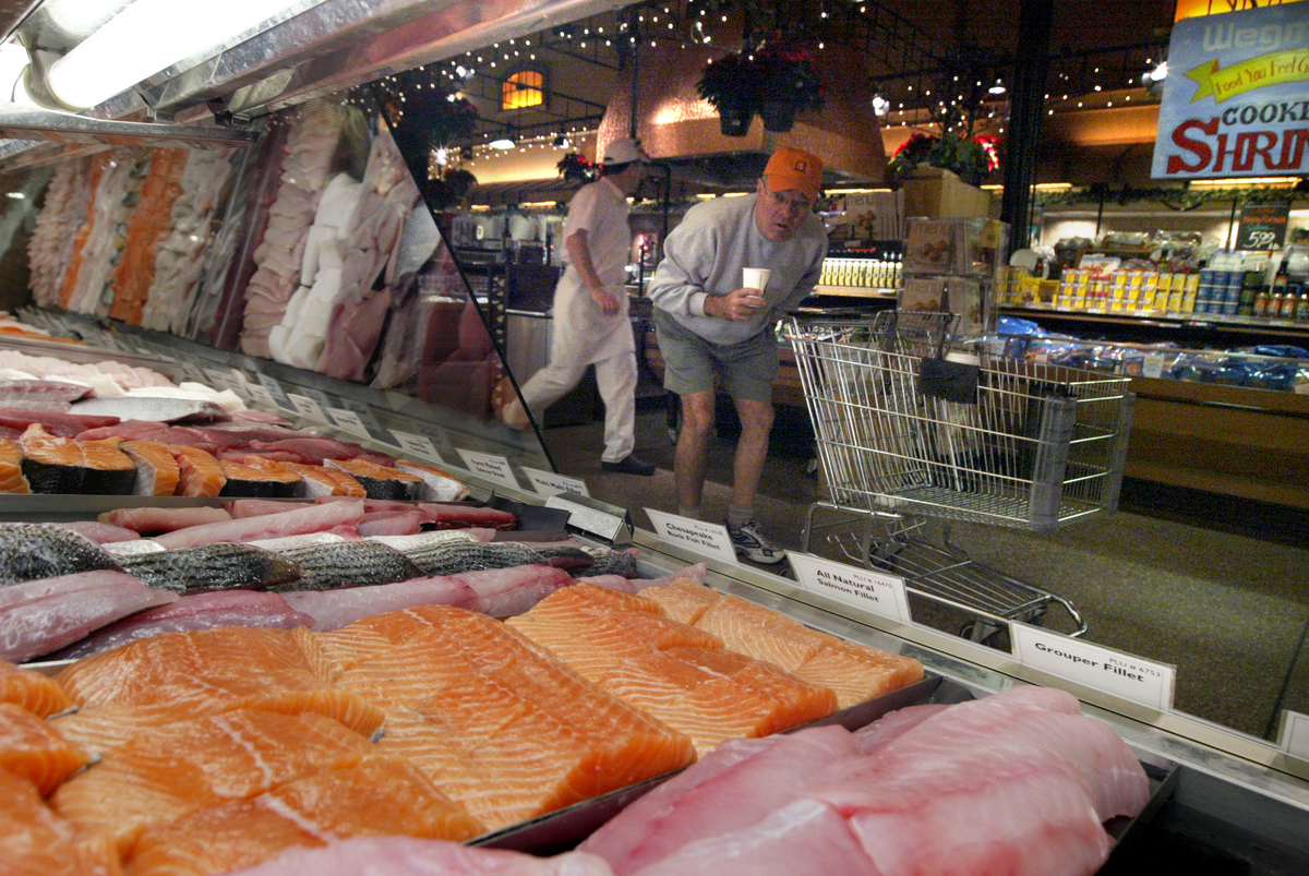 A man shops for farm-raised salmon at a grocery store.