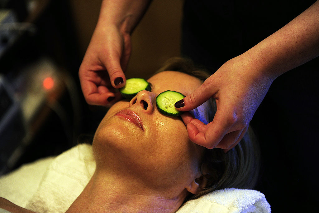 A woman at a spa has cucumber slices placed over her eyes.