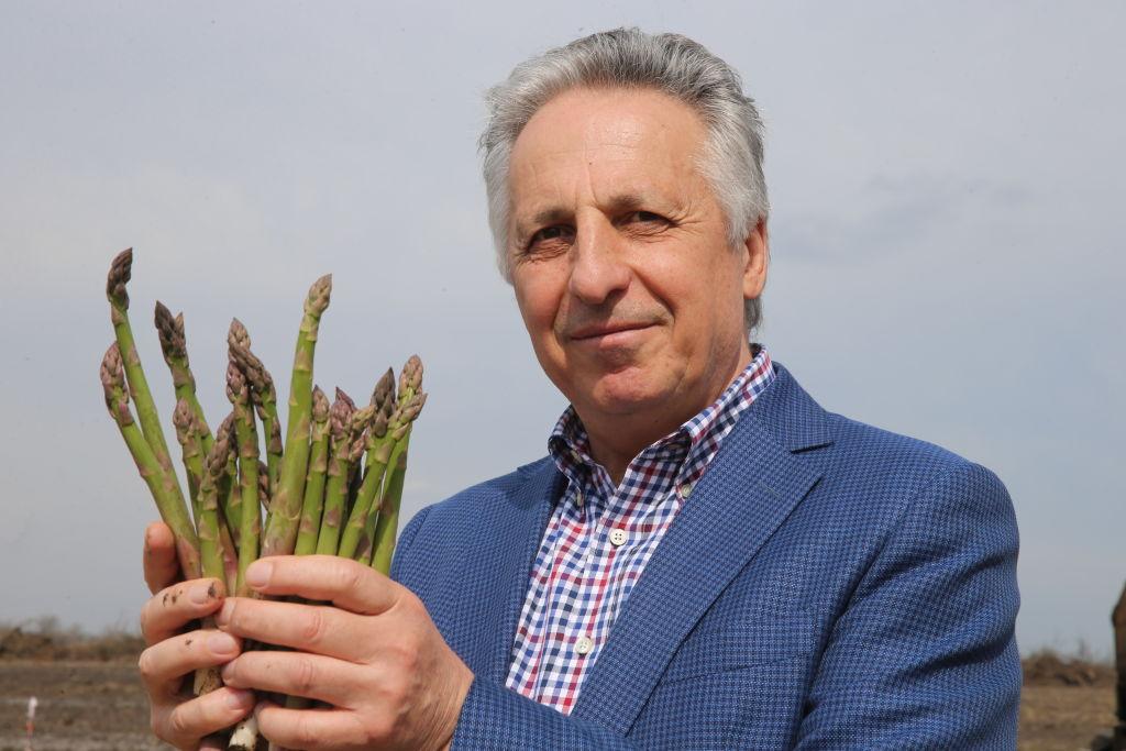 A man holds asparagus.