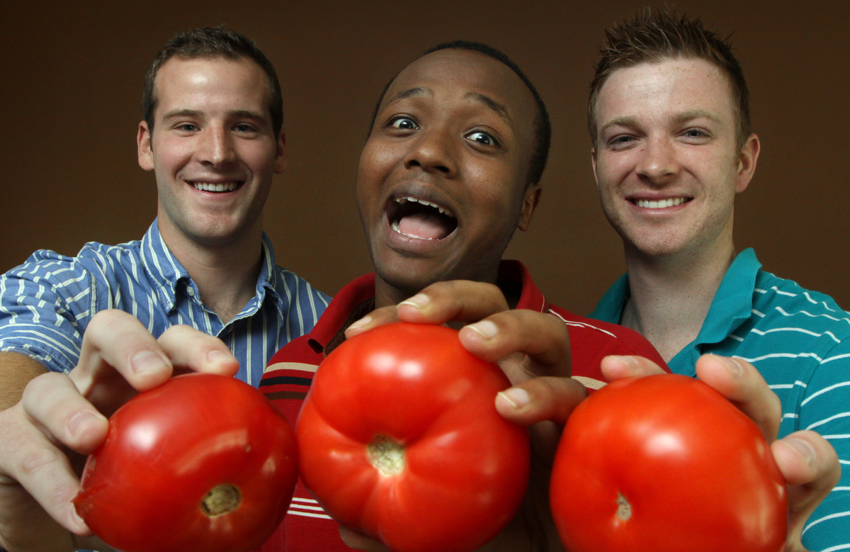 Three men happily hold up tomatoes.
