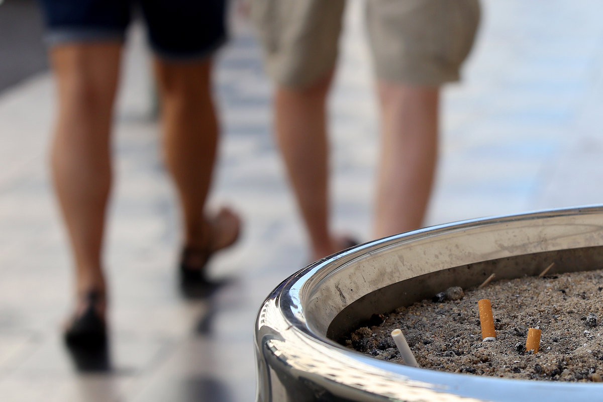 Two people walk away from a public ashtray.