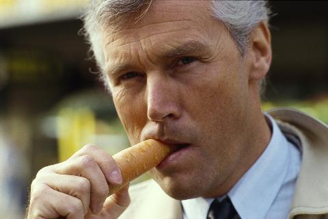 A man eats a carrot.