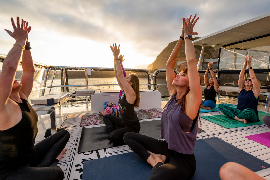 Women practive yoga on a yacht.