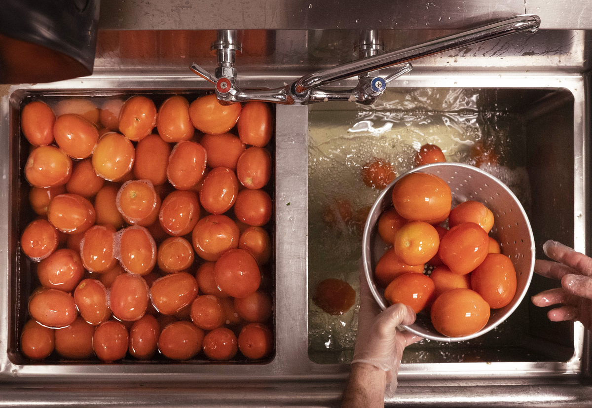 A man pulls a colander of washed tomatoes from a sink.