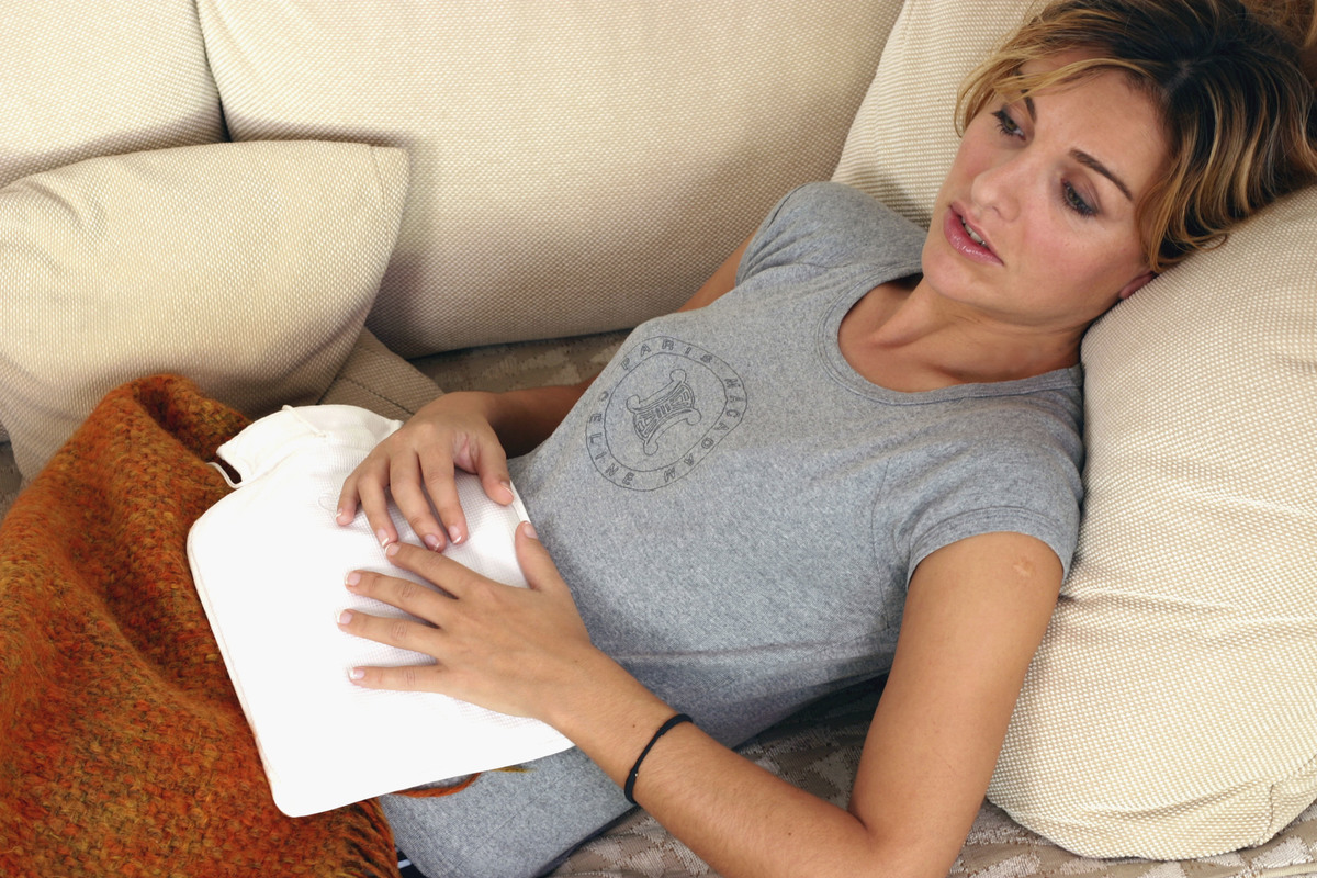 A woman lies on the couch because of abdominal pain.