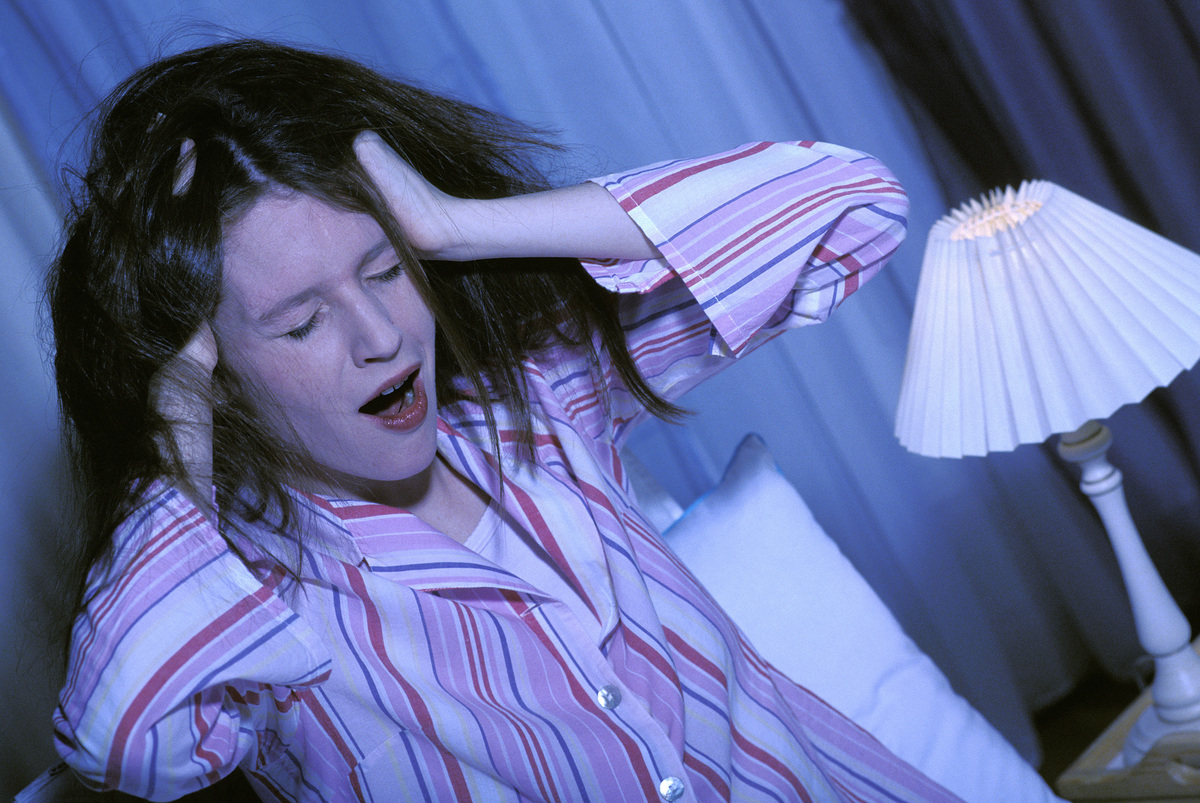 A woman with messy hair yawns while sitting up in bed.