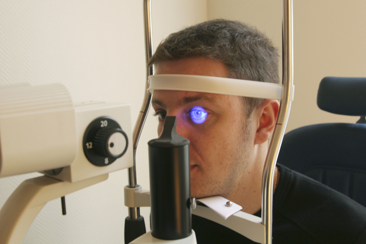 An Optician exams eyes with an ultraviolet lamp.