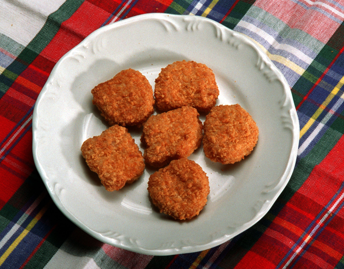 Processed chicken nuggets sit on a plate over a plaid blanket.