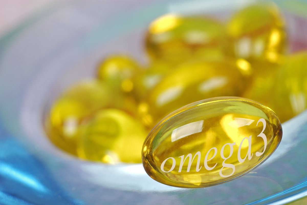 Golden omega-3 supplement capsules are seen.