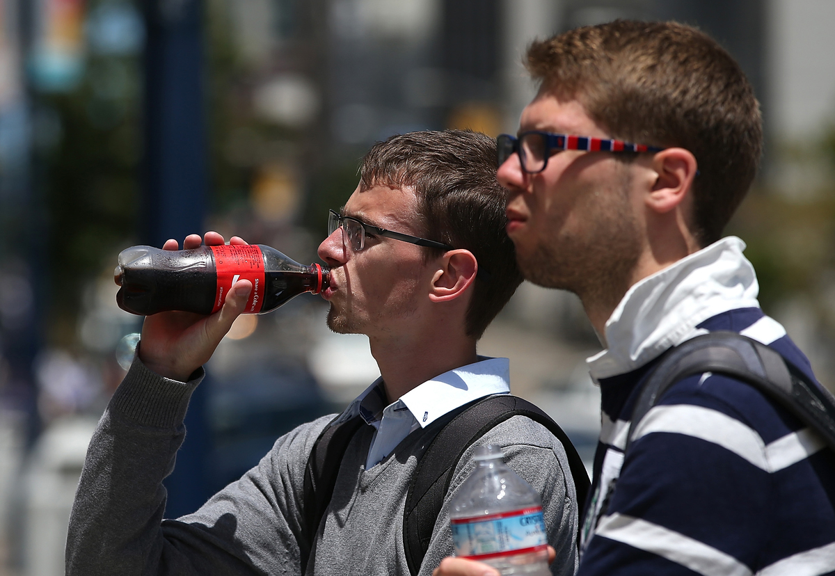 A man drinks a bottle of Coke while walking through San Francisco.