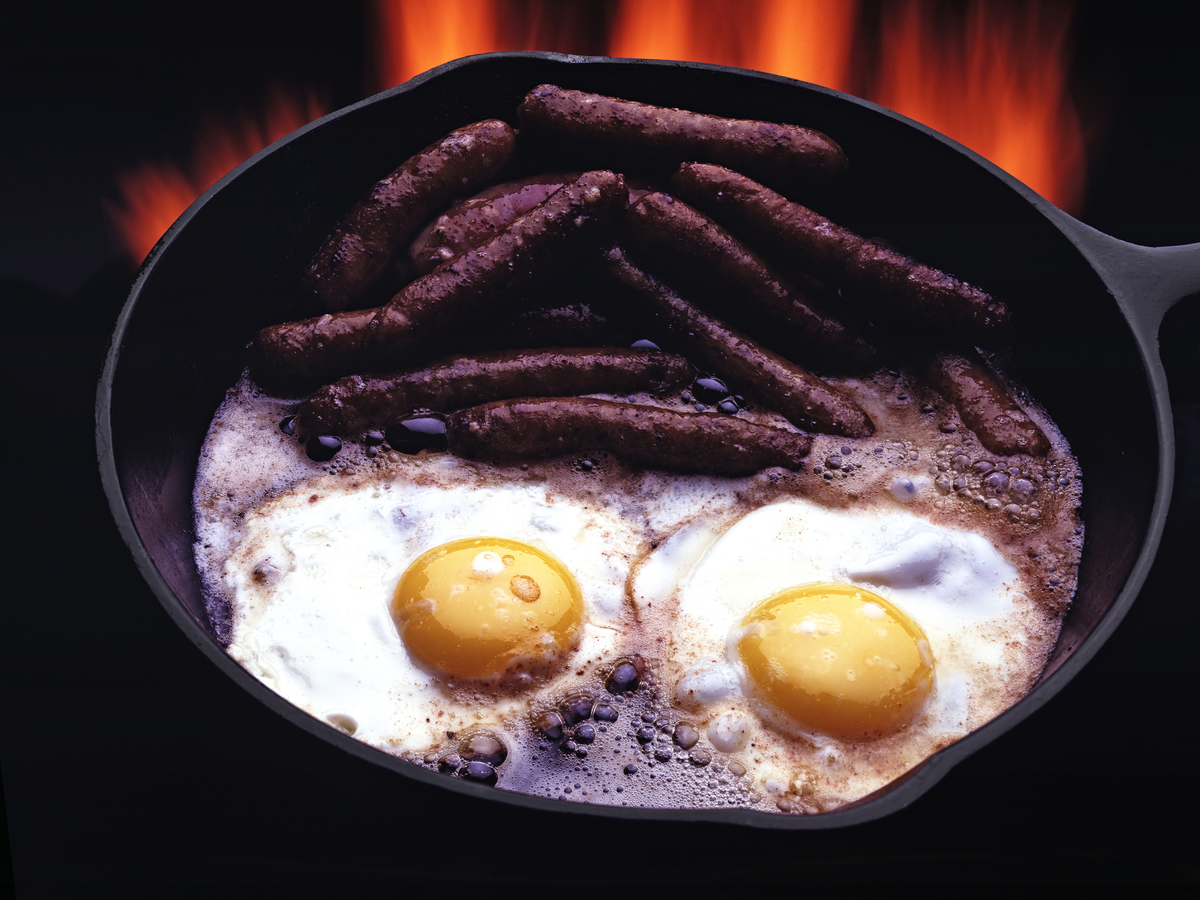 Eggs cook with sausage in a cast iron pan.