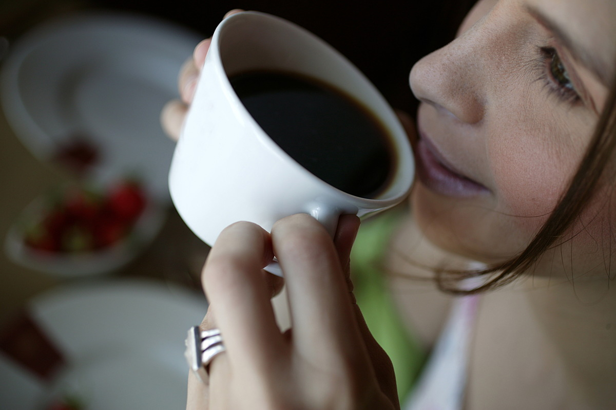 A close-up shows a woman drinking black coffee.