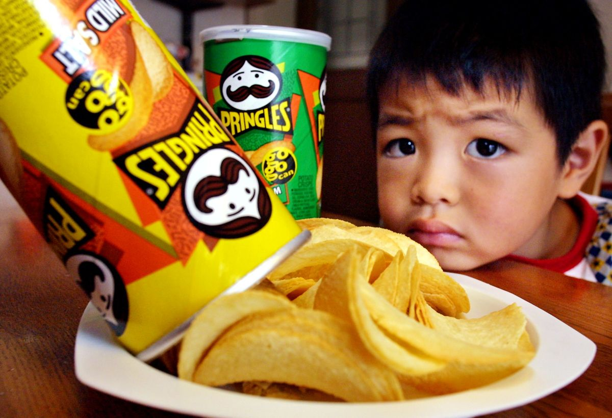 A Japanese boy looks wistfully at the Pringles' potato chips.
