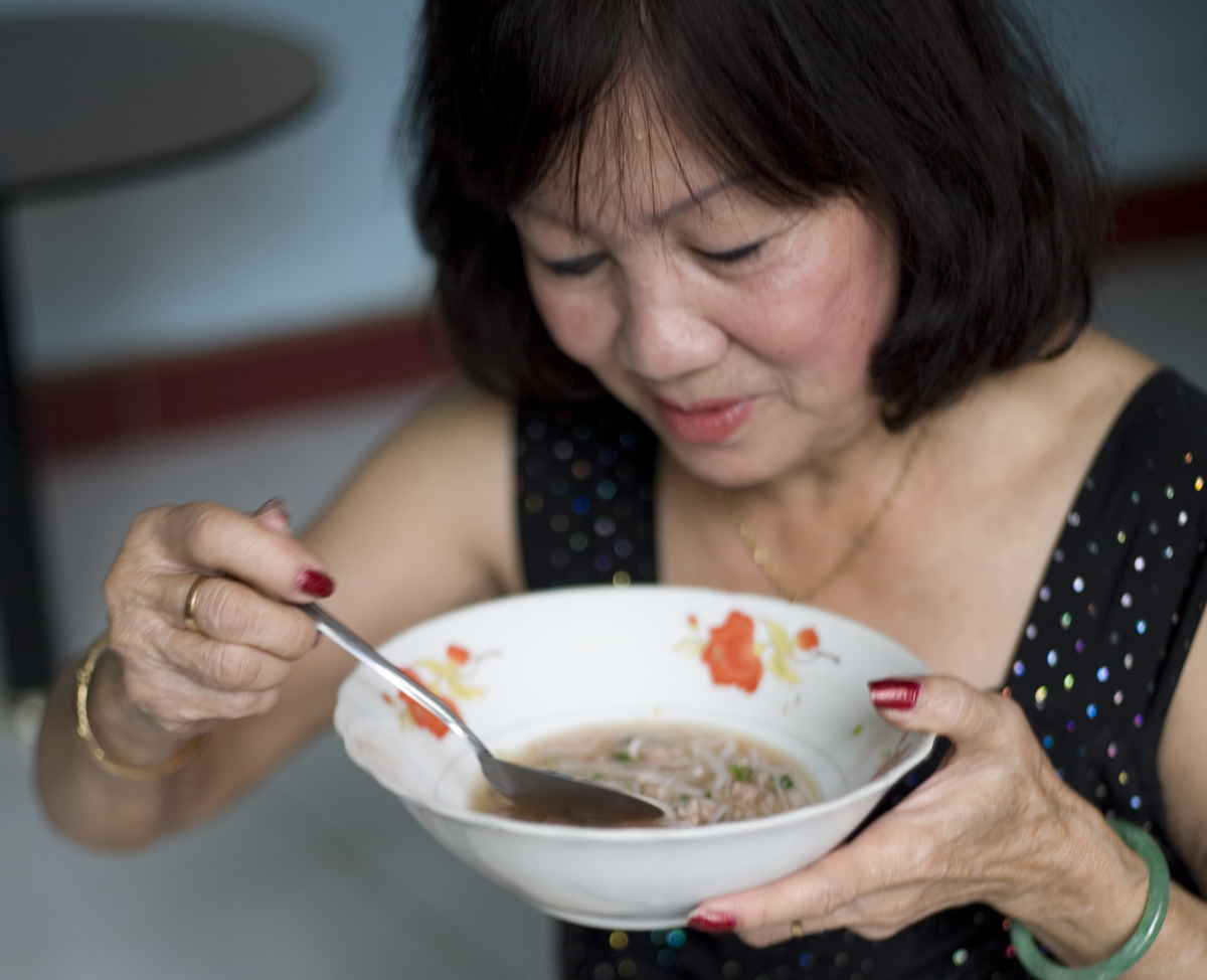 A woman enjoys a dish of Pho noodle soup.
