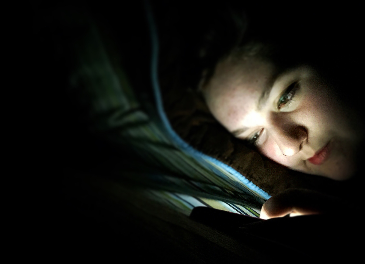 A teenage girl texts in her bed in the dark.
