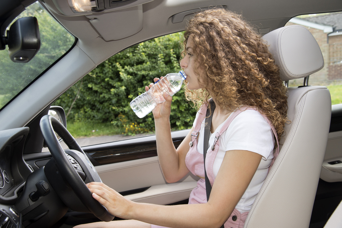 A woman drinks from a water bottle while driving.