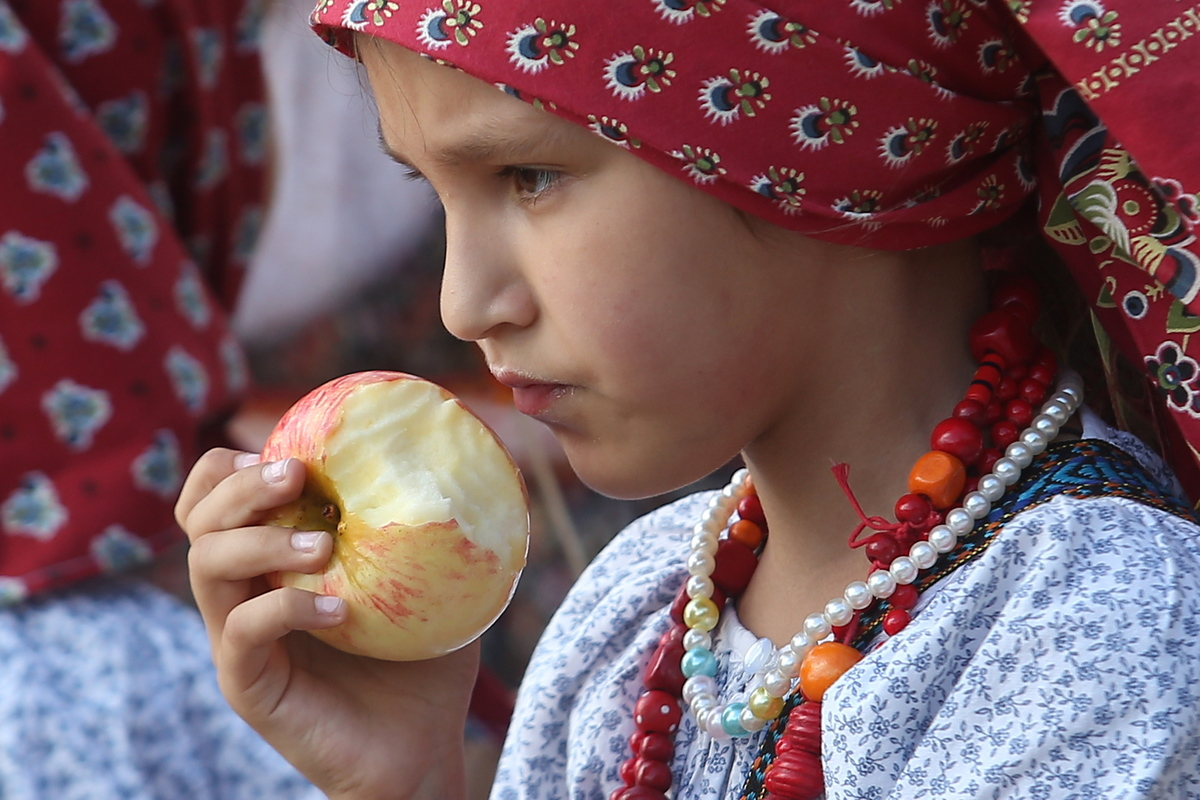 A girl eats an apple during an ethnic music festival.