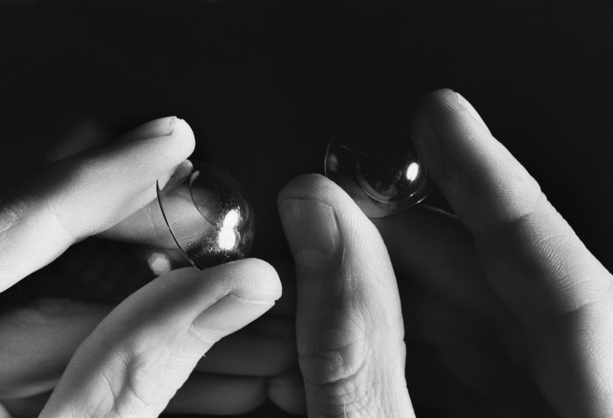 A person holds a pair of contact lenses.