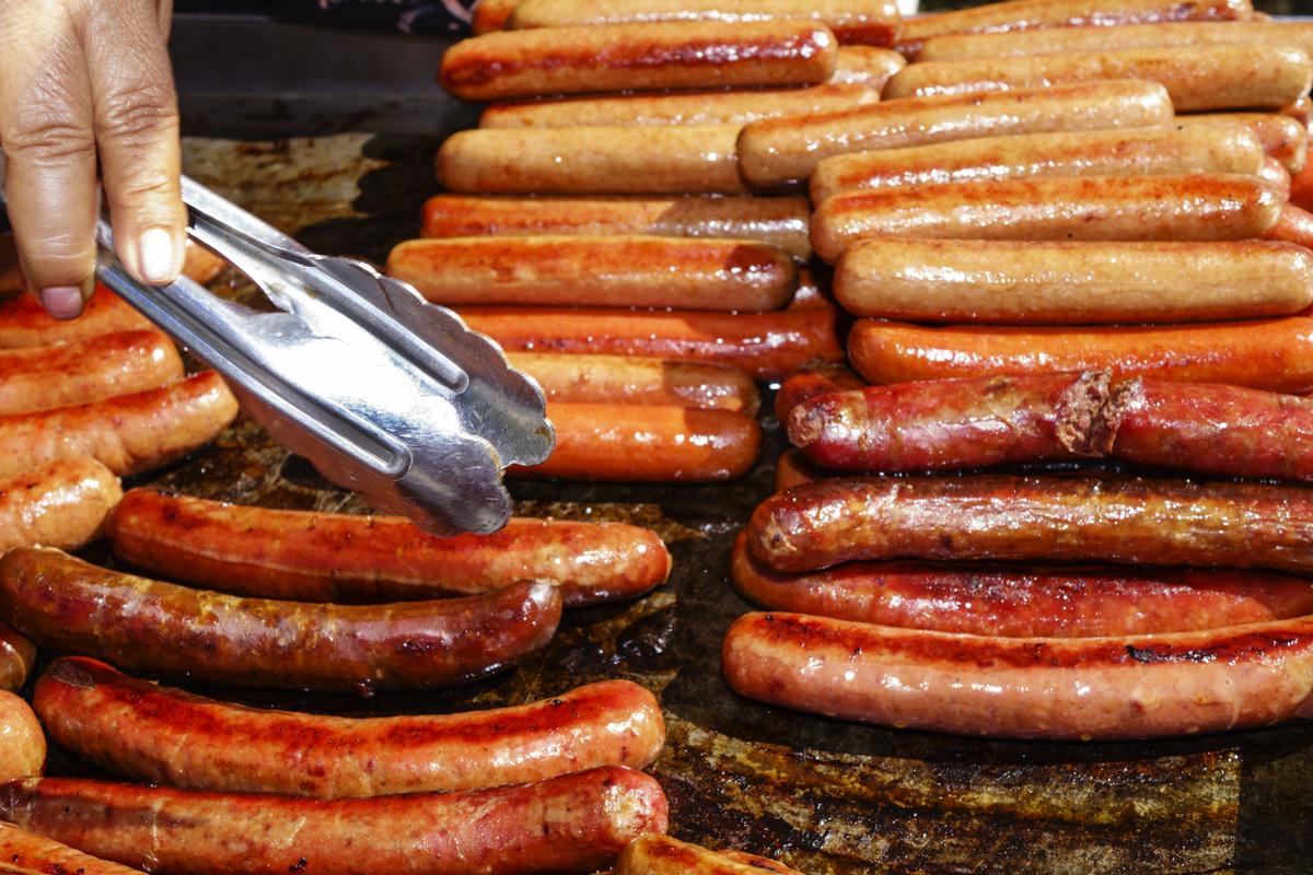 A food vendor grills hot dog.