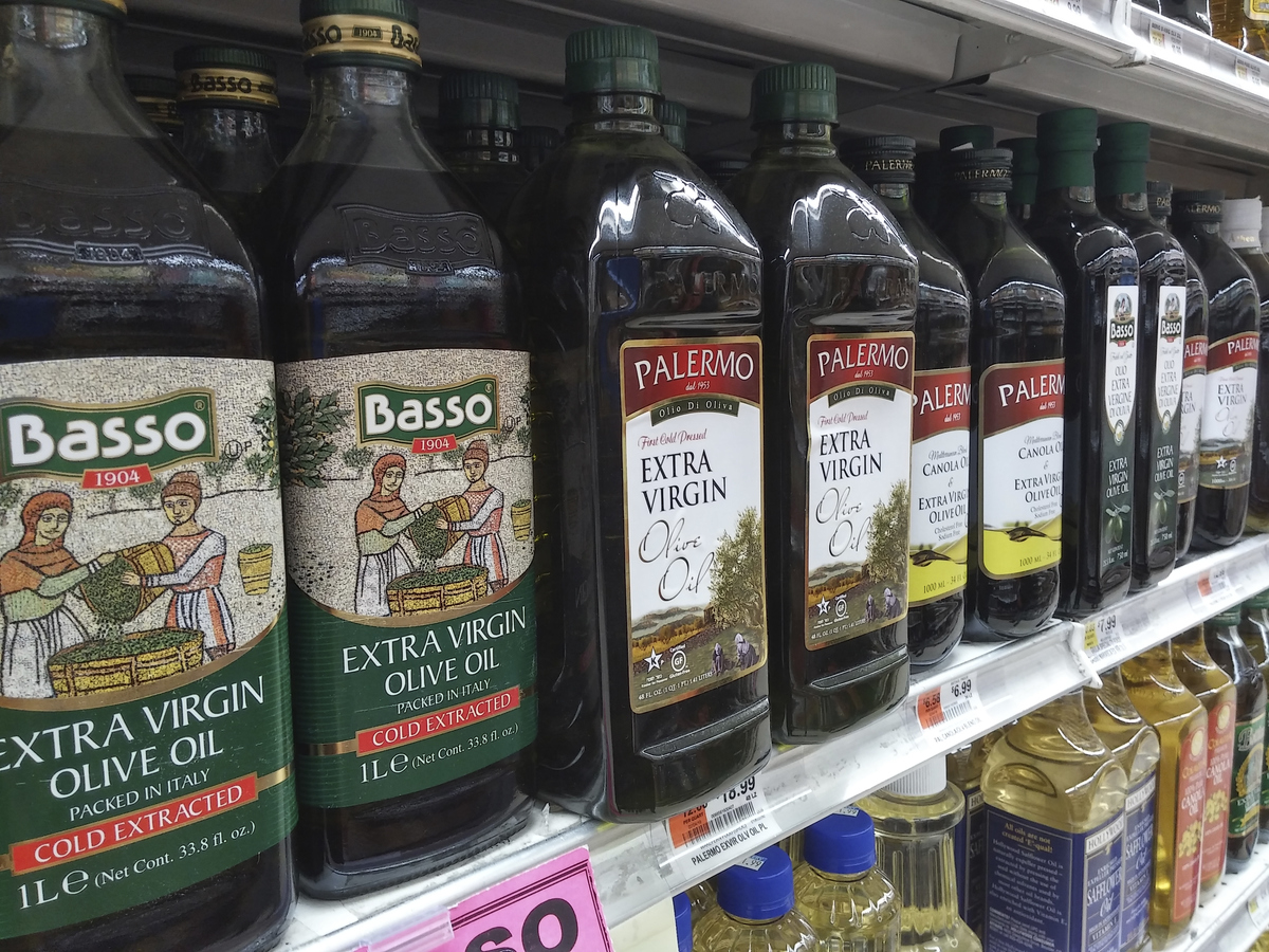 Bottles of imported olive oil and olive oil blends are seen on a supermarket shelf.