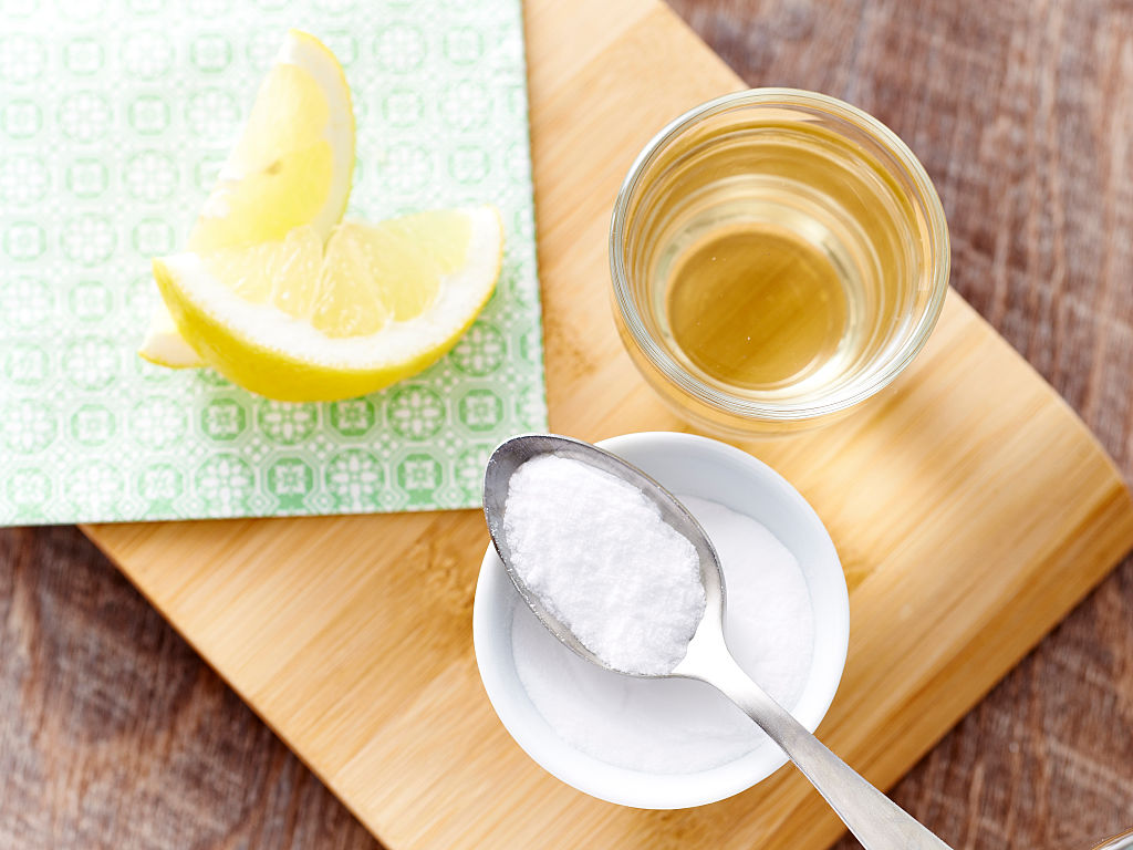 A spoonful of baking soda is pictured next to water and lemon.