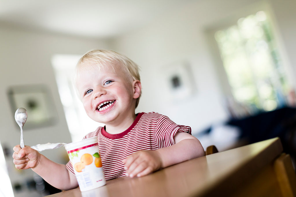 A toddler eats yogurt.