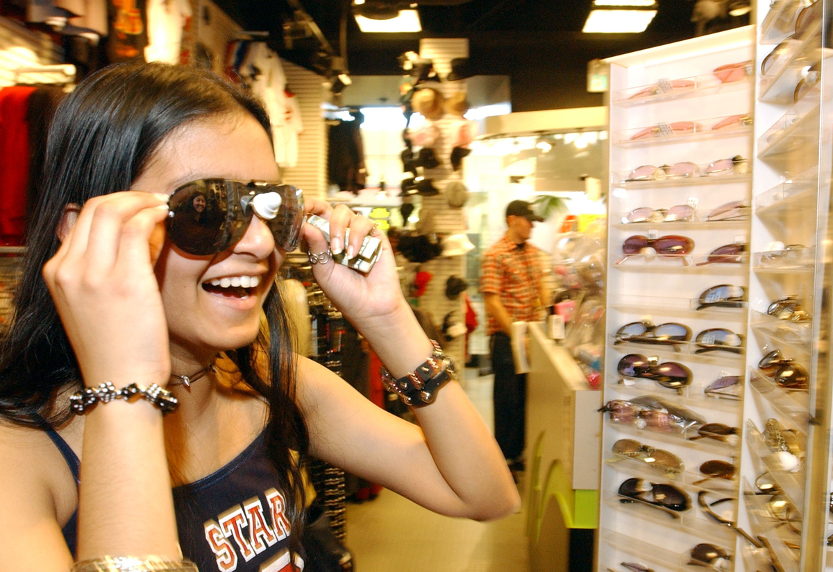 A customer tries on sunglasses in a Hot Topic.
