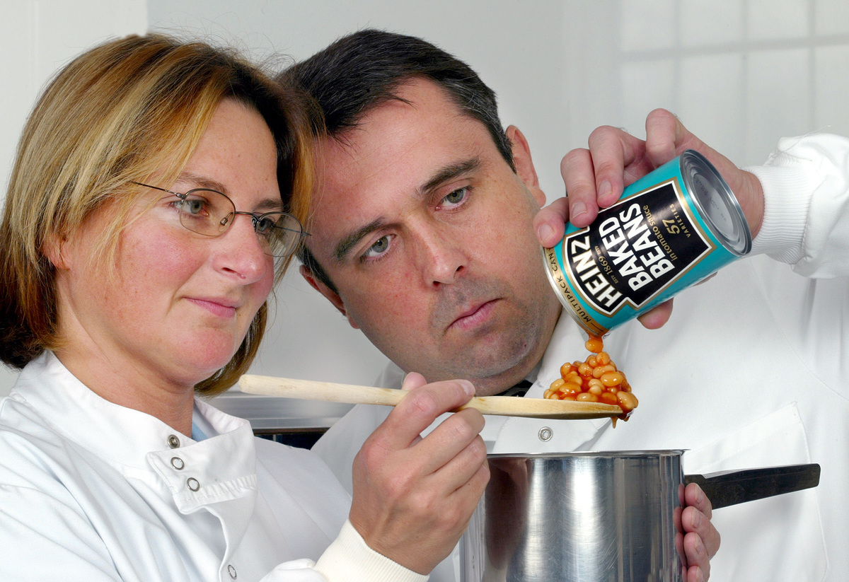 Chefs measure Heniz baked beans on a spoon.