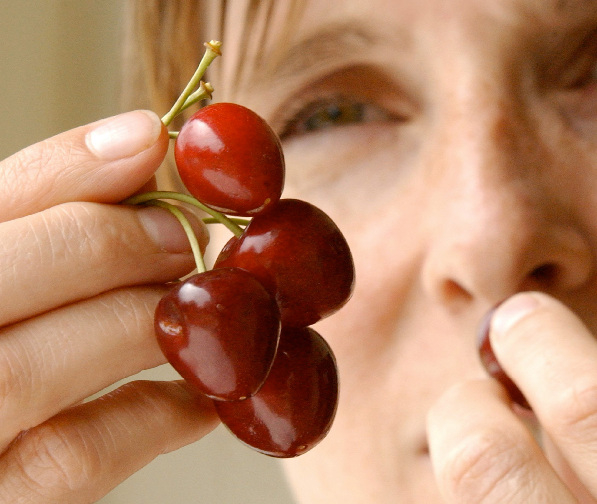 A woman eats cherries in this close-up.