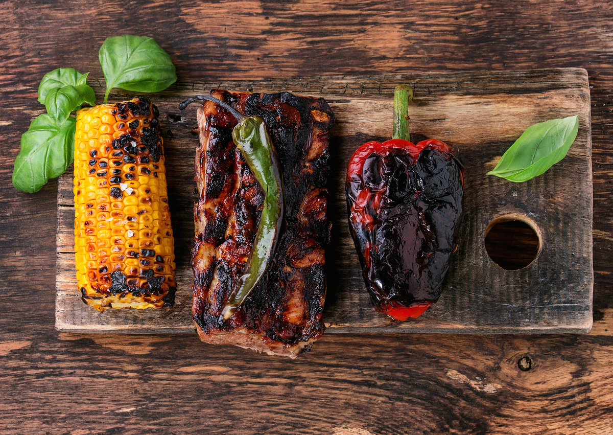 BBQ grilled pork ribs, corn, green chili and a red bell pepper are served on wooden chopping board.