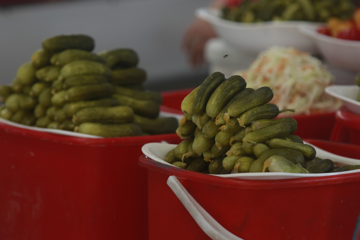 Pickles are stacked in red buckets.