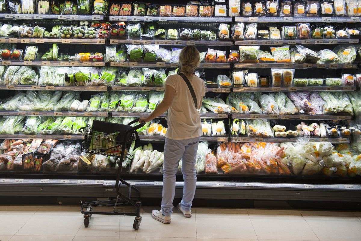 A shopper looks at a shelf of vegetables wrapped in plastics at a grocery store.