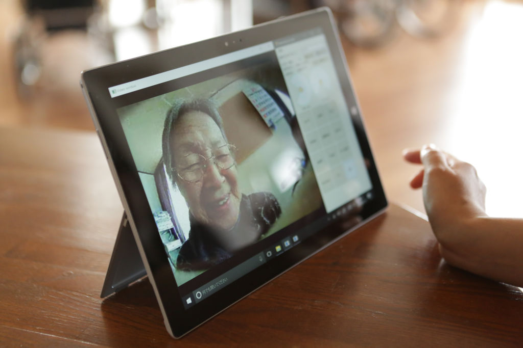 The screen shows the image of an elderly user