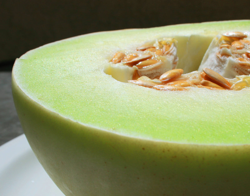 Honeydew and its seeds are seen close-up.