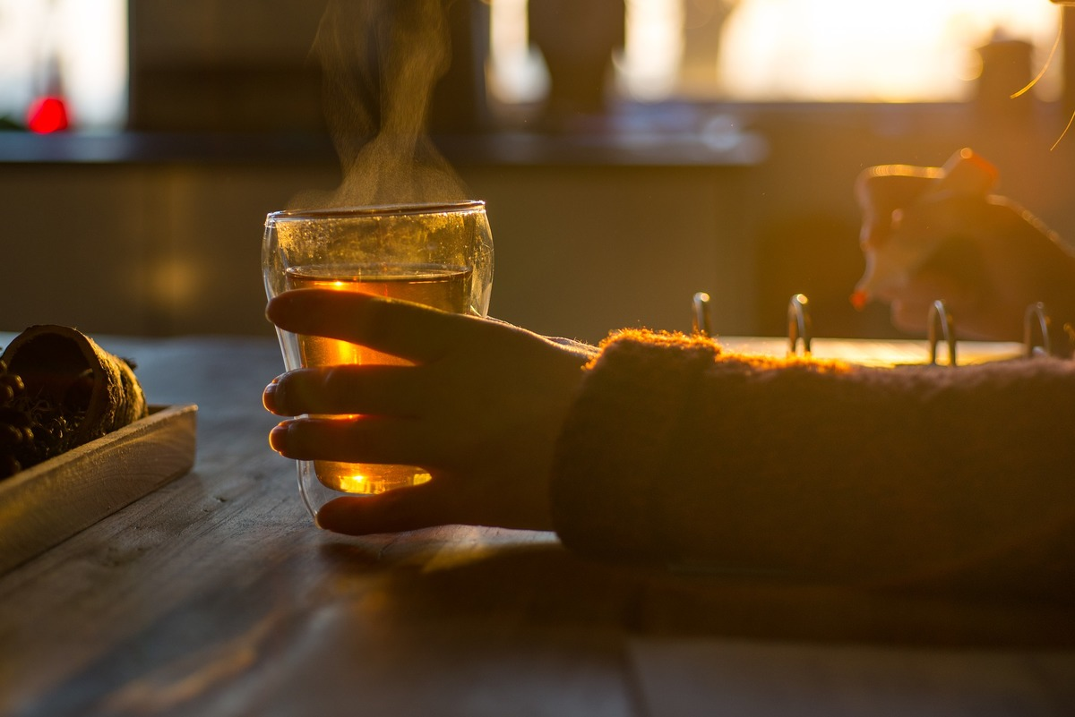 A person holds a glass of steaming green tea on a table.