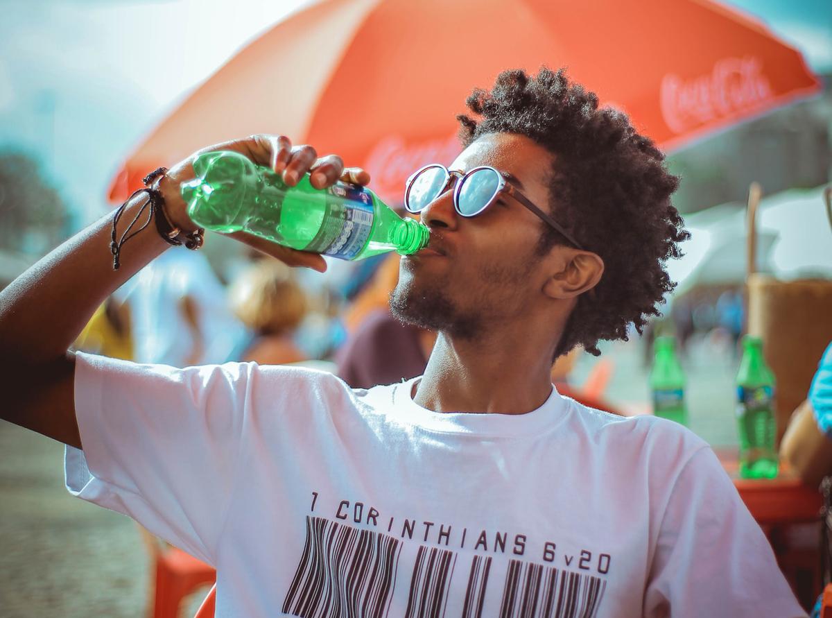 A man drinks soda on the beach.