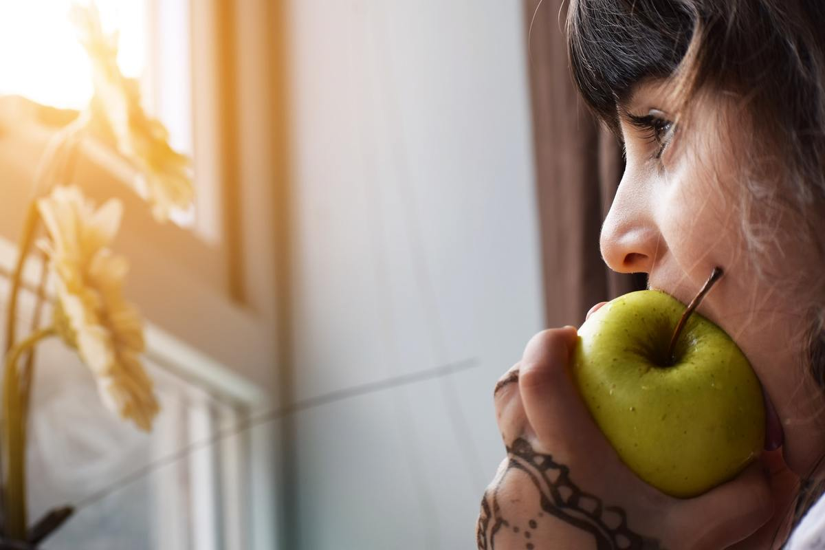A woman bites into a green apple while looking out the window.