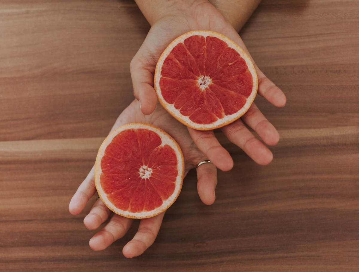 A woman holds two halves of grapefruit.