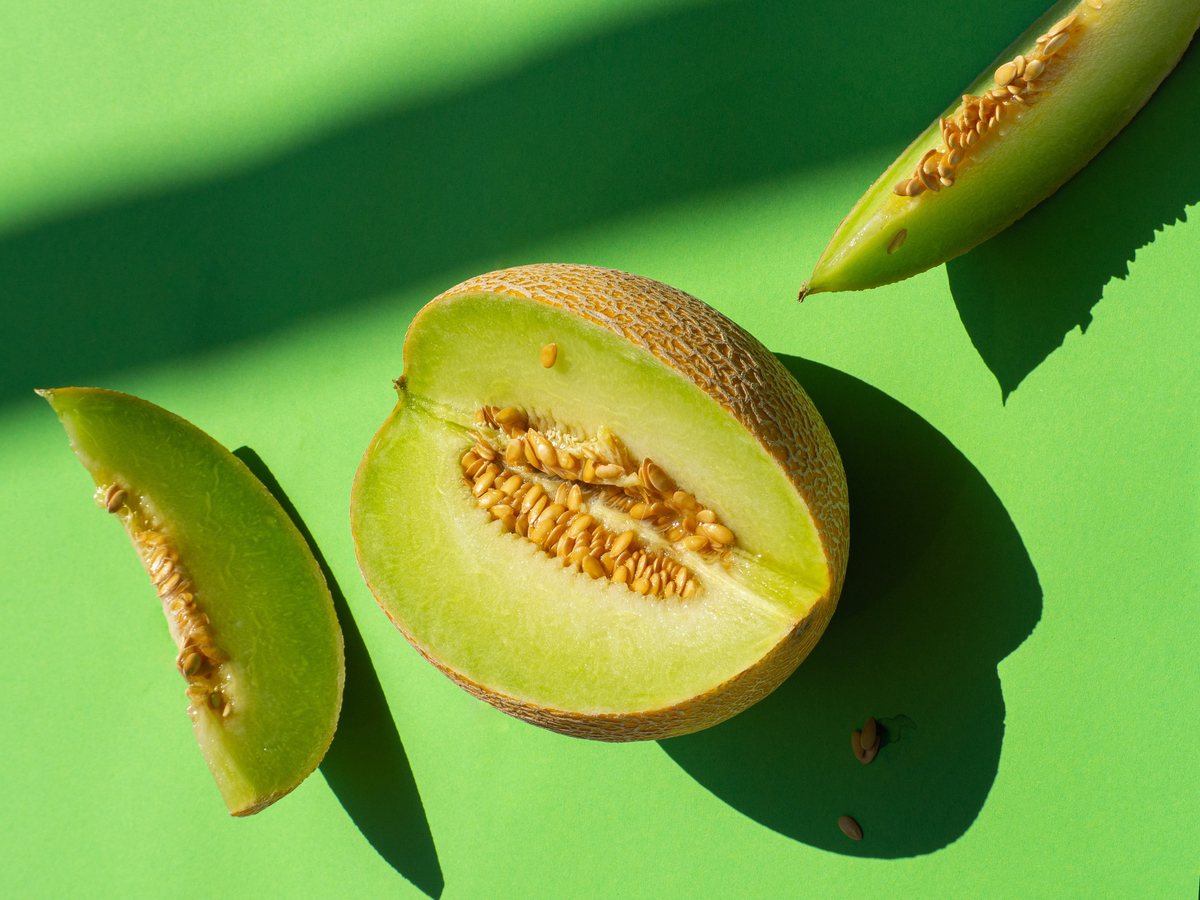 Sliced honeydew lies against a green background.