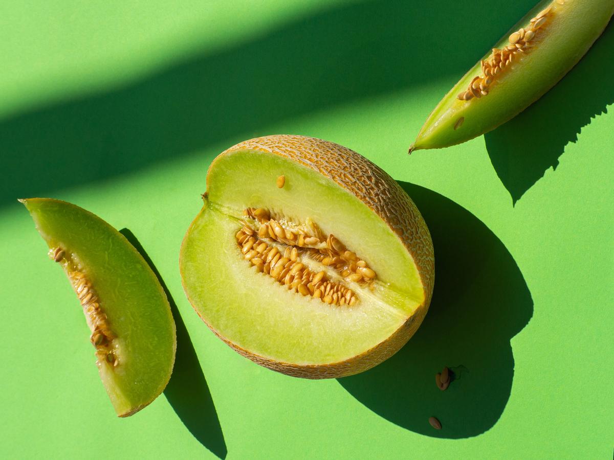 Sliced honeydew lies against a green background.