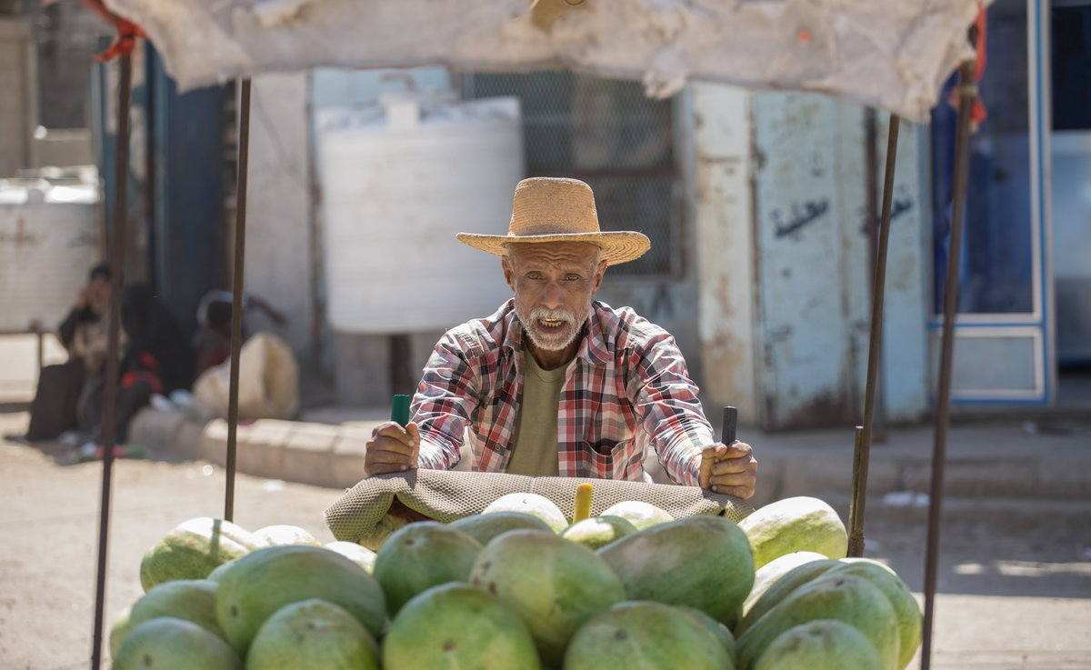 A seller moves a cart of honeydew melons in Yamen.