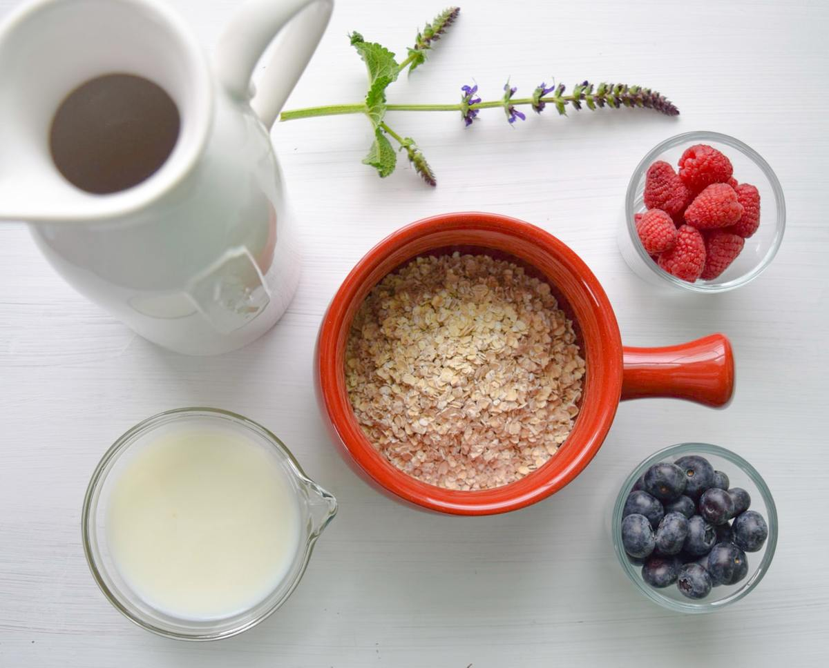 A bowl of oatmeal joins a pitcher of milk and berries.