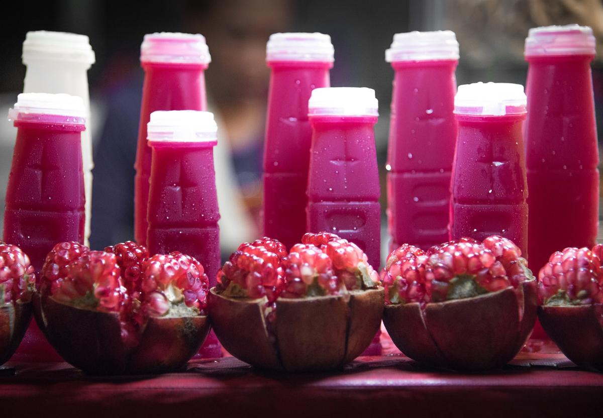 Bottles of pomegranate juice stand behind sliced pomegranates.