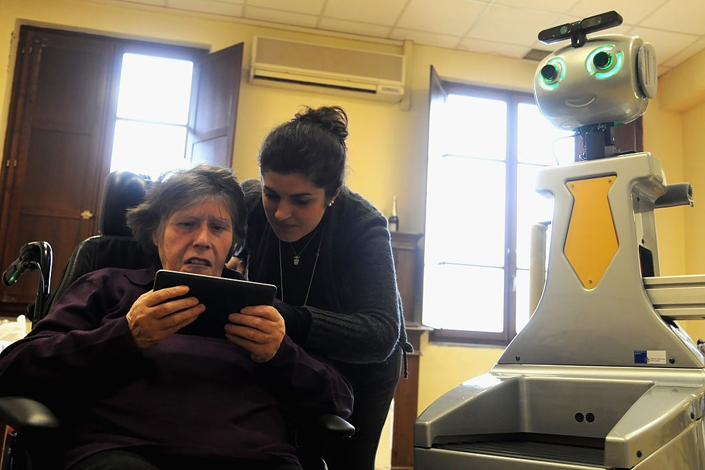 A professional educator at nursing residence San Lorenzo helps an eldery lady to carry out daily cognitive stimulation activities with the robot of the project Robot-Era