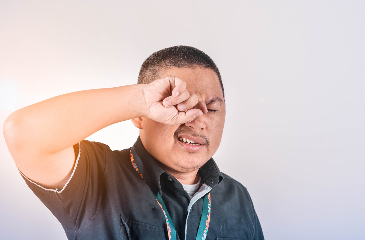A man rubs his eyes to assuage an itch.