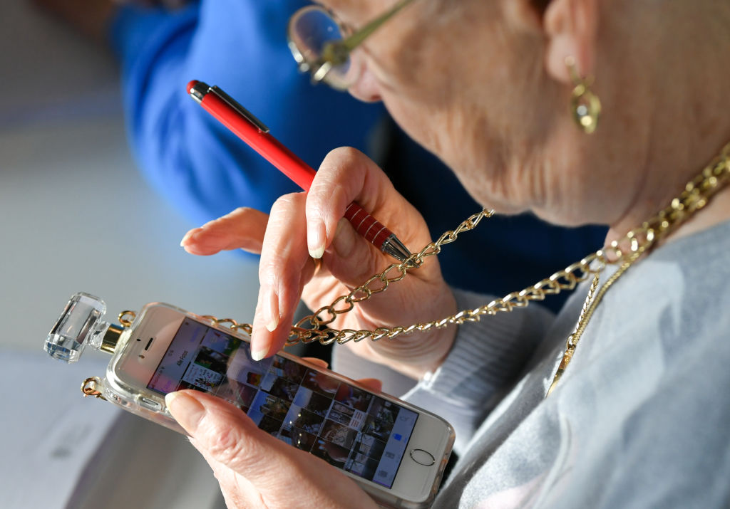 A senior watches her smartphone