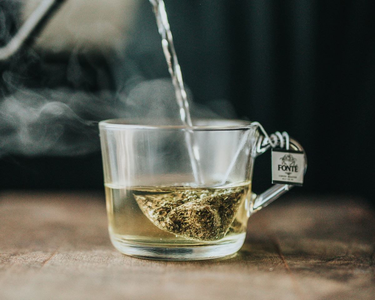 A person pours hot water into a mug with a tea bag.