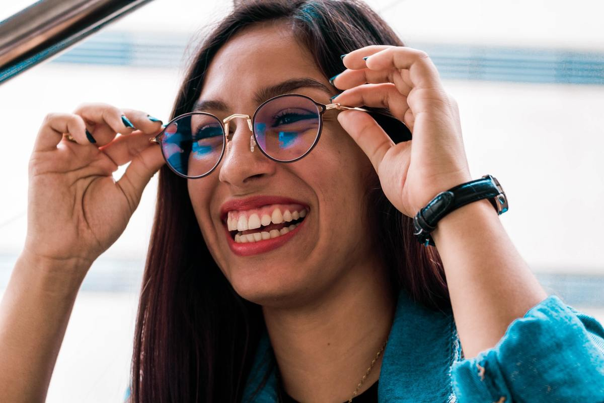 A woman smiles as she puts on her glasses.