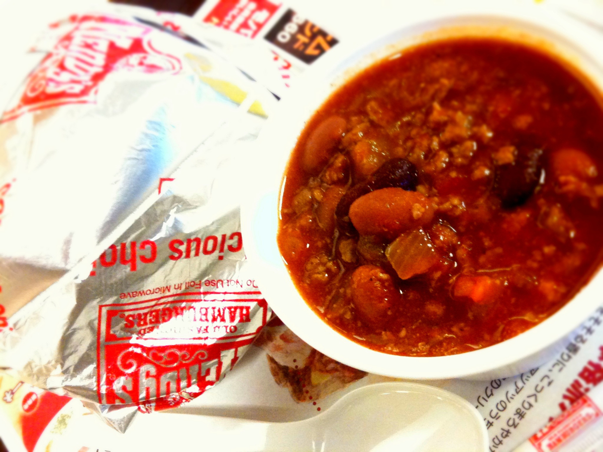 A small bowl of Wendy's chili sits next to a burger.